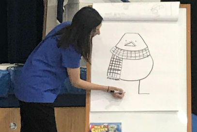 Author, Angela Dominguez, drawing on white chart paper