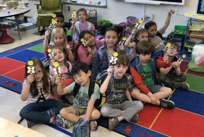 Students holding bee puppets