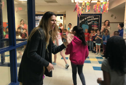 Mrs. Homan gives high fives to students during the clapout