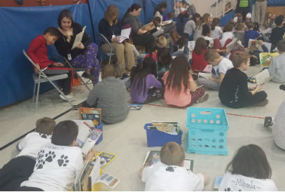 Students and teachers reading in the gym