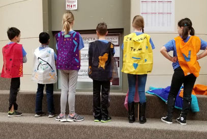 student dressed in different colored capes
