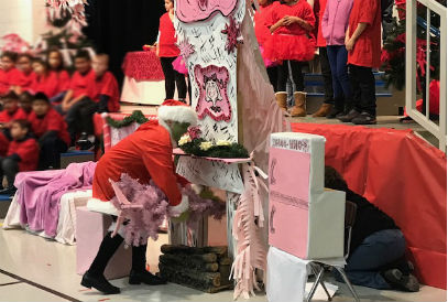 Student dressed as the Grinch putting a pink Christmas tree up a chimney