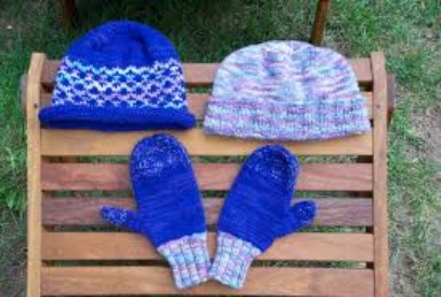 2 wool hats and a set of mittens on a wooden table