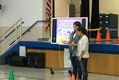 Ms. Godoy and Mrs. Mossholder reading a book during the assembly