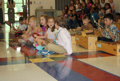Kindergarten students sing and play instruments