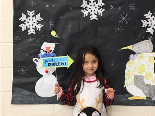 student posing for a photo in the penguin photo booth