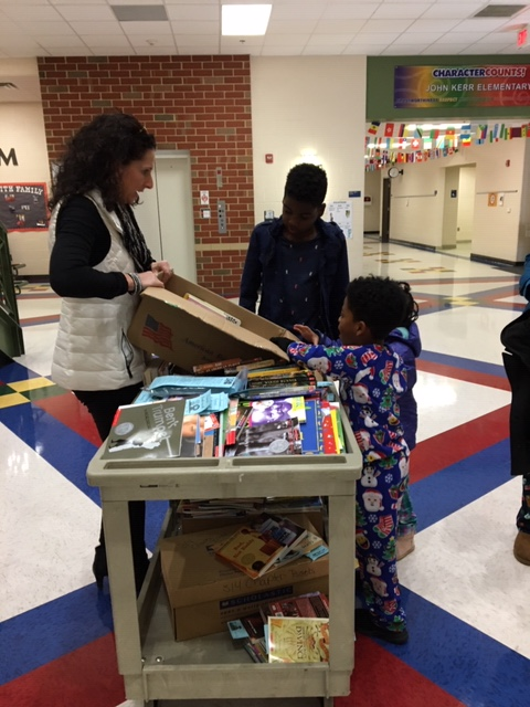 Ms. Ford showing students books for the free book table