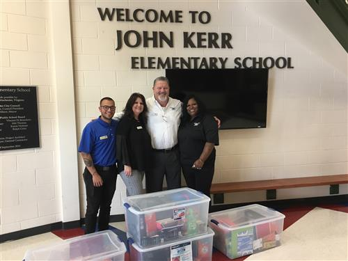 "Employees of Malloy Chevrolet pose under ""Welcome to John Kerr Elementary School"" in front of plastic bins of school supplies"