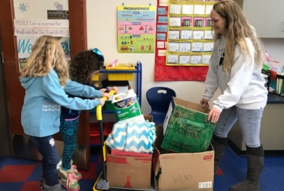Students help a representative from the SPCA move a cart of donations