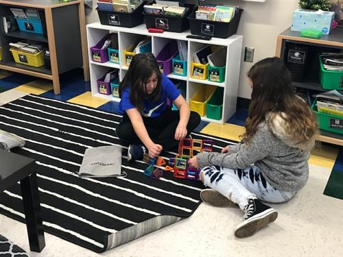 students building with magnetic tiles