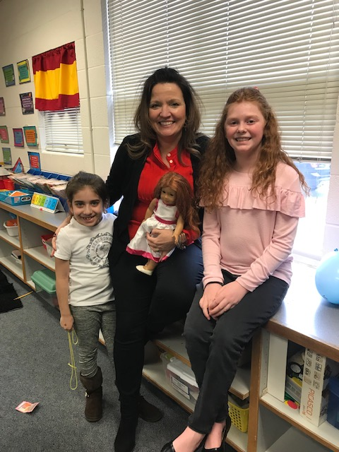 Mrs. Downey holding an American Girl doll posing with two students