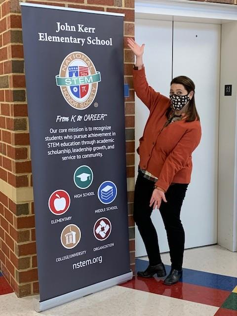 Mrs. Thomas posing by the National Stem Honor Society Banner