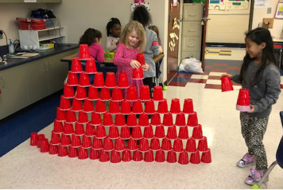 students building a pyramid with 100 red plastic cups
