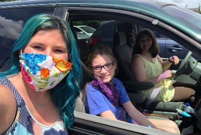 Teacher wearing a face mask with student and family in car
