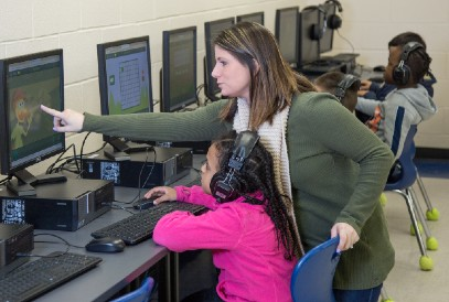 teacher pointing to a comptuer screen and students using computers