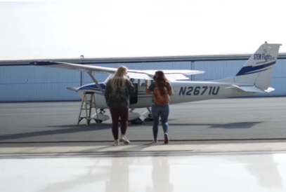 two people walking toward a small airplane