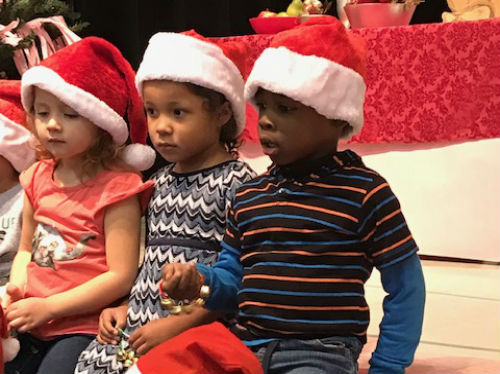 PreK students wearing Santa hats and ringing jingle bells