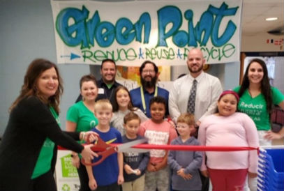 Students and adults standing in front of Green Point Recycle Banner while Mrs. Downey cuts a ribbon