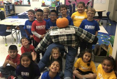 Students gathered around a scarecrow with a pumpkin head