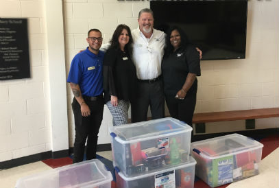 Employees of Malloy Chevrolet pose in front of bins of school supplies