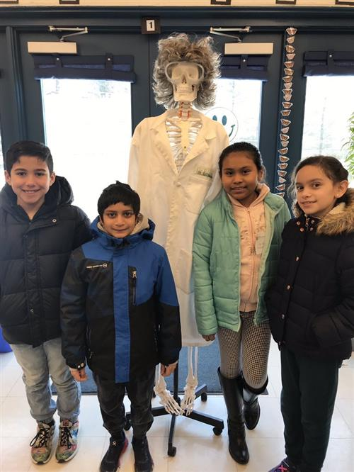 FDES students posing in front of a skeleton dressed as a scientist.