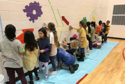 students painting the gym wall